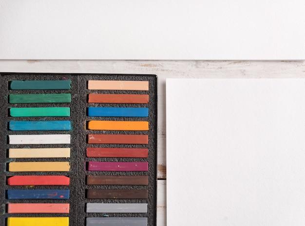 Boîte avec peinture pastel colorée sur papier blanc