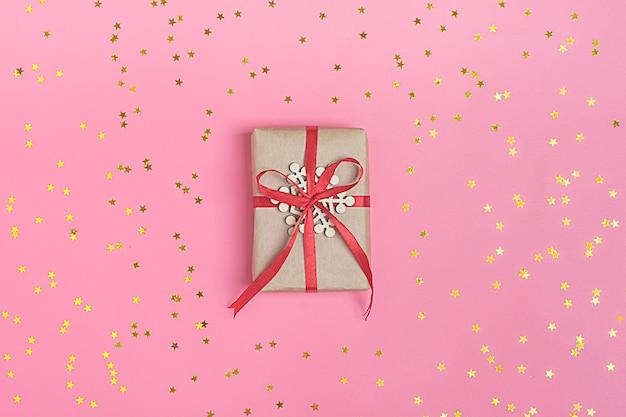 Boîte, pépites d'étoiles dorées. vacances de fête, fond rose. concept de célébration vue de dessus