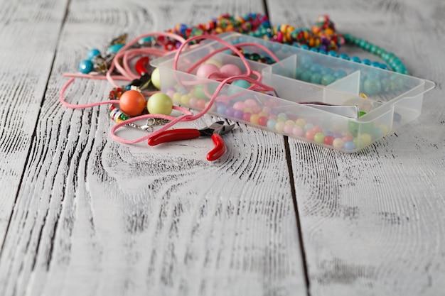 Boîte avec perles, pince et coeurs en verre pour créer des bijoux faits à la main sur du vieux bois