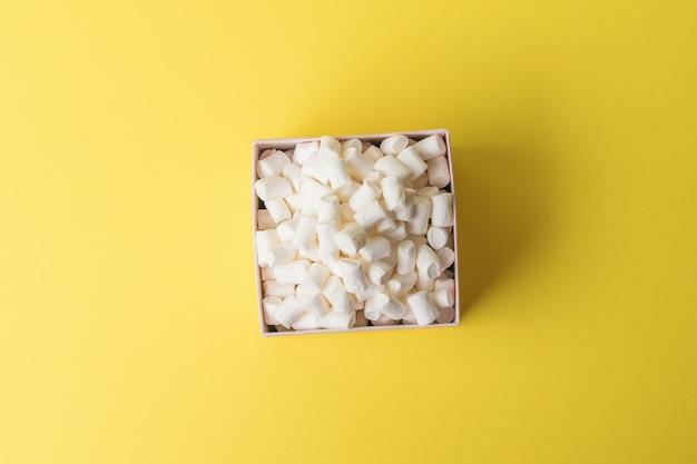 Une boîte avec une petite guimauve sur fond jaune. un régal sucré. mise à plat.