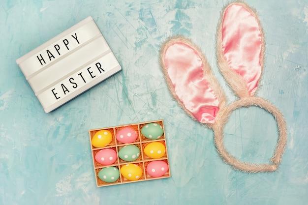 Boîte avec petits oeufs peints, oreilles de lapin et lightbox avec joyeuses pâques