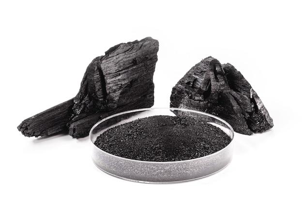 Boîte de pétri avec charbon de bois en poudre à côté d'un morceau de charbon de bois, surface blanche isolée