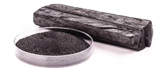 Boîte de pétri avec du charbon en poudre à côté d'un morceau de charbon de bois, surface blanche isolée