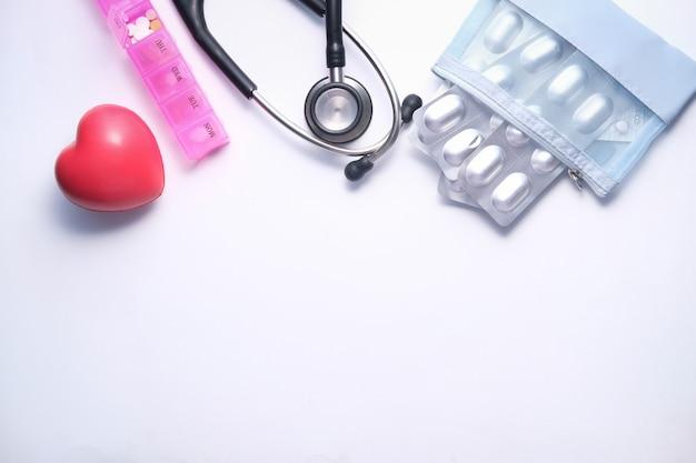 Boîte à pilules, coeur et stéthoscope sur espace blanc