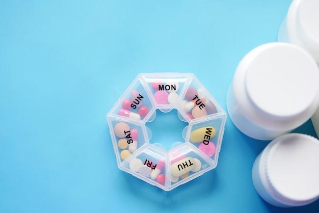 Boîte à pilules de médecine et conteneur sur fond bleu