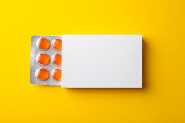 Boîte à pilules vide sur fond jaune, vue de dessus