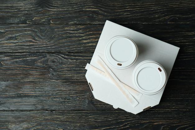 Boîte à pizza et gobelets en papier sur une surface en bois