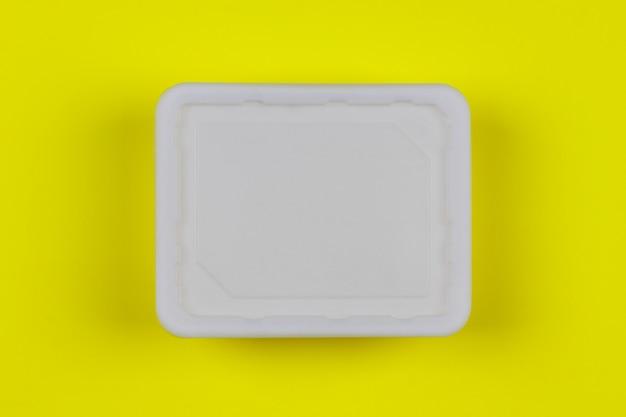 Boîte en plastique blanc maquette sur la vue de dessus de fond jaune