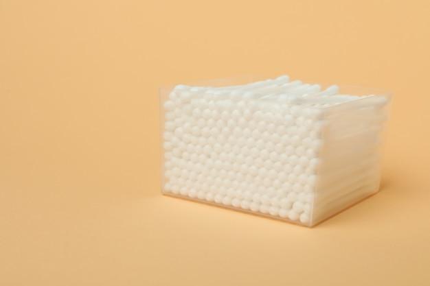 Boîte en plastique avec des cotons-tiges sur fond beige