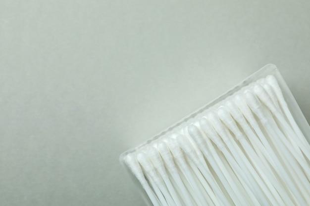 Boîte en plastique avec des cotons-tiges sur fond gris clair