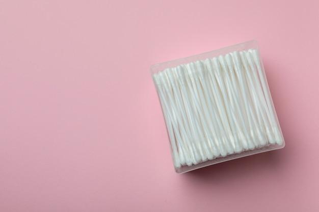 Boîte en plastique avec des cotons-tiges sur fond rose