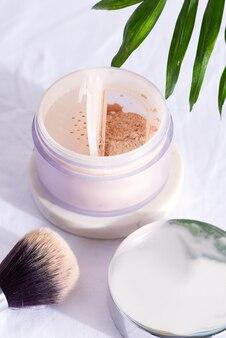 Boîte en plastique avec poudre pour le visage et pinceau pour le maquillage sur un fond textile blanc avec des feuilles de palmier vertes.