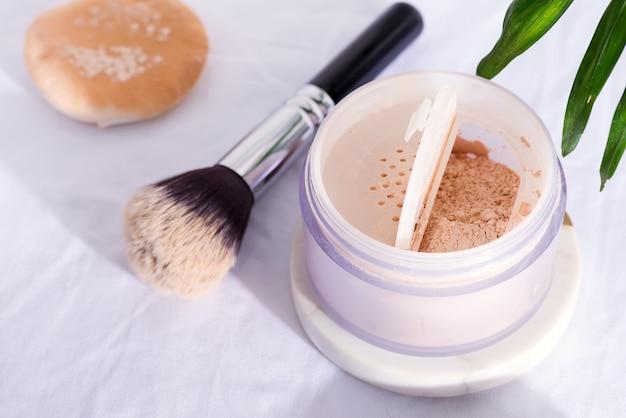 Boîte en plastique avec poudre pour le visage et pinceau pour le maquillage