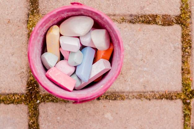Boîte en plastique, seau de craie colorée sur l'asphalte.