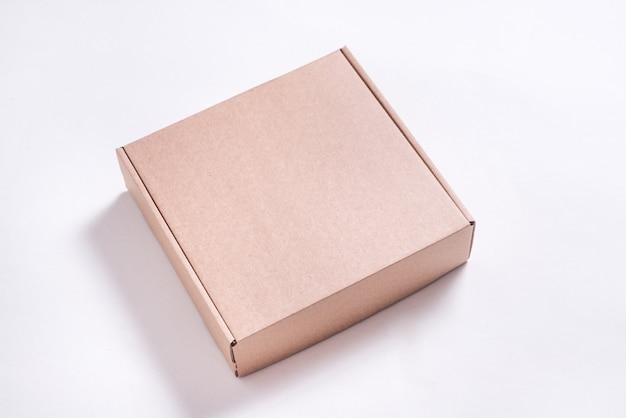 Boîte plate en carton marron sur fond blanc