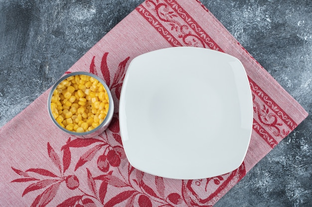 Une boîte pleine de graines de maïs soufflé avec une assiette vide sur une nappe.