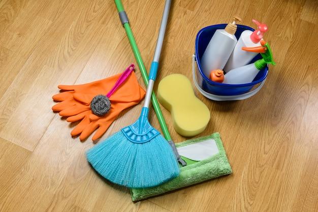 Boîte pleine de produits de nettoyage, vadrouille, balai et gants sur fond de plancher en bois