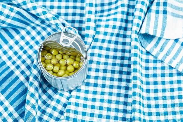Une boîte avec des pois verts bouillis sur une nappe bleue.