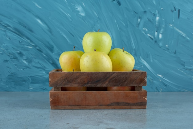 Une boîte de pommes fraîches , sur le fond de marbre. photo de haute qualité