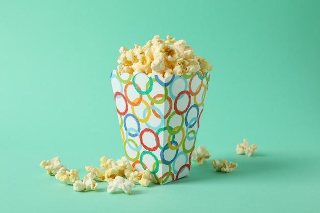 Boîte avec pop-corn sur espace menthe. nourriture pour regarder le cinéma