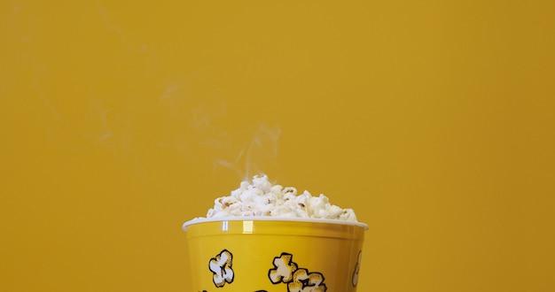 Boîte de pop-corn sur fond jaune.