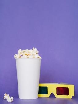 Boîte de pop-corn salé avec des lunettes 3d sur la table
