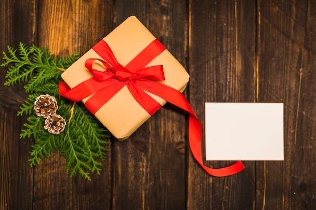 Boîte présente avec un arc rouge près du rameau de conifères et du papier