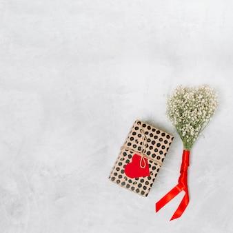 Boîte présente avec coeur de papier d'ornement près de la plante avec ruban