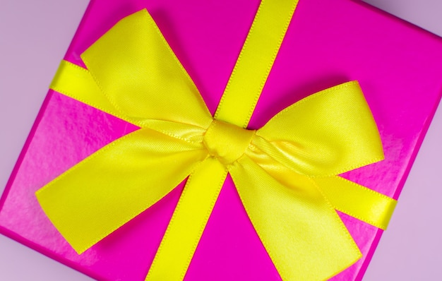 Boîte présente avec noeud jaune sur fond rose. fêtes d'anniversaire. vente et remise. idées d'achats de noël. offre spéciale. espace de copie. notion de vendredi noir.