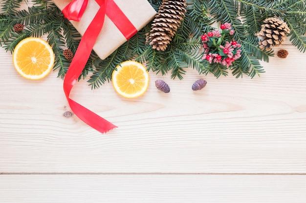 Boîte présente près d'une branche de sapin ornée et d'oranges
