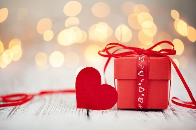 Boîte présente rouge avec ruban rouge et coeur de papier sur une table en bois,