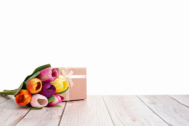 Boîte présente et tulipes sur table rustique en bois avec fond blanc
