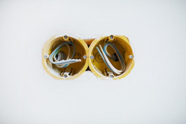 Boîte de prise filaire en mur blanc, concept de construction ou de rénovation, espace de copie
