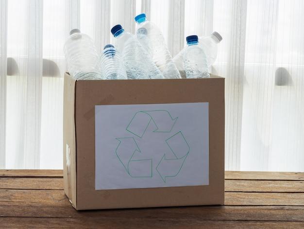 Boîte de recyclage remplie de récipients en plastique transparent