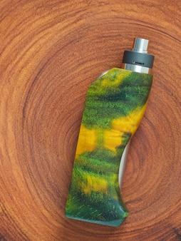 Boîte régulée en bois de peuplier stabilisé vert jaune régulée mods avec atomiseur dégouttant reconstructible sur fond de texture en bois naturel