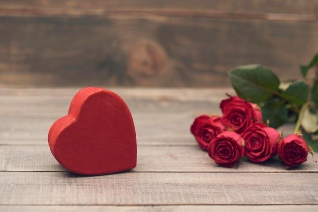 Boîte rouge en forme de coeur sur le bois