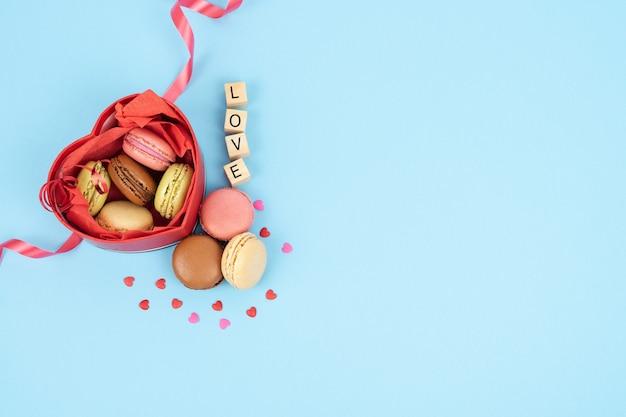Boîte rouge en forme de cœur ouvert plein de macarons
