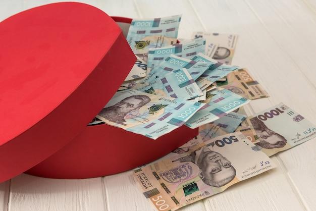 Une boîte rouge en forme de cœur pleine d'argent. uah argent de l'ukraine 1000 et 500 billets sur deskv