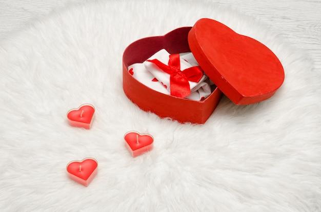 Boîte rouge ouverte avec du lin blanc et rouge en forme de cœur, une fourrure blanche. bougies en forme de coeur