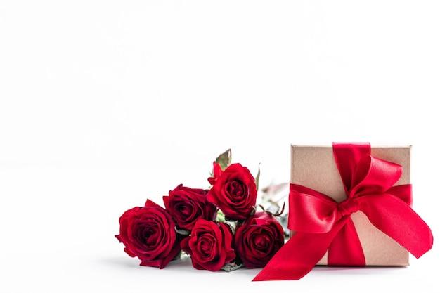 Boîte rouge avec des roses sur une surface blanche