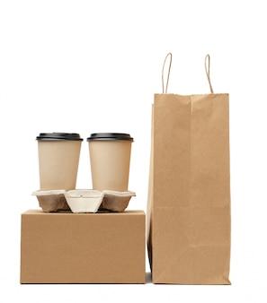 Boîte, sac en papier brun et gobelets jetables pour boissons chaudes dans le bac sont isolés sur fond blanc