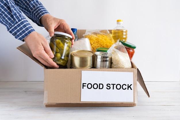 Boîte avec stock de nourriture. boîte en carton avec beurre, conserves, céréales et pâtes. réserve.