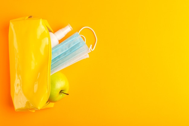 Boîte de stylo jaune vue de dessus avec spray apple et masque sur la surface orange