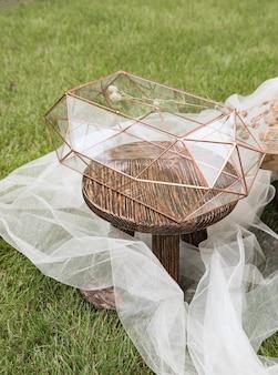 Boîte en verre de mariage pour enveloppes pour salutations sur petite table en bois et tissu blanc avec des plantes comme décoration