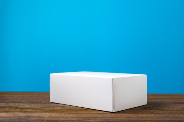 Boîte vide en carton blanc sur bois