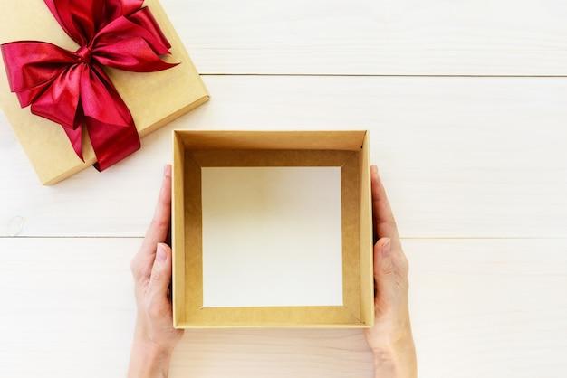 Boîte vide pour un cadeau entre les mains d'un homme. orientation horizontale, vue de dessus, espace de copie.
