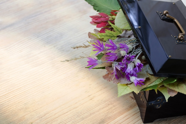 Boîte vintage avec des feuilles d'automne et des fleurs sauvages à l'intérieur.