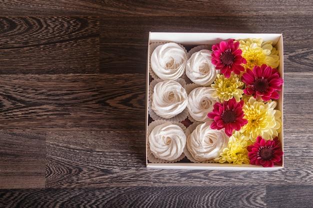 Boîte avec zéphyr blanc et tournesols et chrysanthèmes