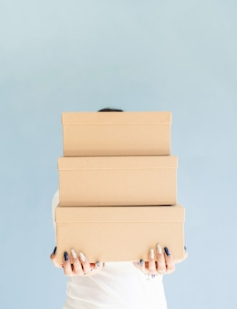Boîtes d'artisanat dans les mains de la femme belle femme souriante tenant des boîtes vierges