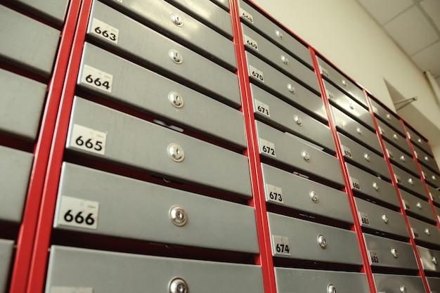 Boîtes aux lettres en acier dans un immeuble résidentiel. même rangées de boîtes aux lettres numérotées. concept de correspondance en ville. vous pouvez l'utiliser comme arrière-plan pour votre création. espace de copie